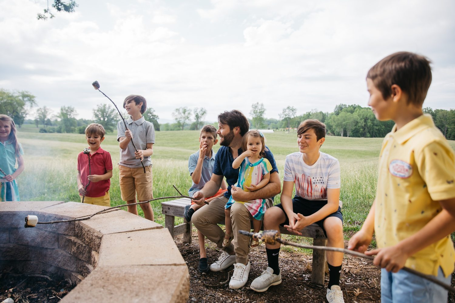 matthew chambers roasting marshmellows in an open field with his kids in virginia
