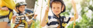 young boy on ropes course at summer camp